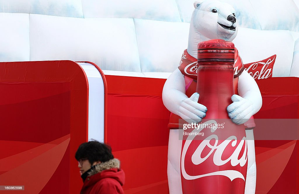 A Coca-Cola Co. event employee walks past the company's promotion booth at the 2013 Pyeongchang Special Olympics Winter Games in Pyeongchang, South Korea, on Wednesday, Jan. 30, 2013. The 2013 Pyeongchang Special Olympics Winter Games takes place from Jan. 29 to Feb 5. Photographer: SeongJoon Cho/Bloomberg via Getty Images