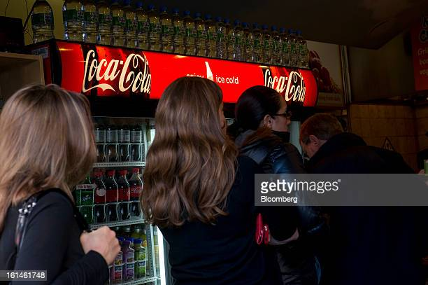 CocaCola Co signage is displayed on a refrigerator as customers stand in line at a restaurant in San Francisco California US on Wednesday Feb 6 2013...