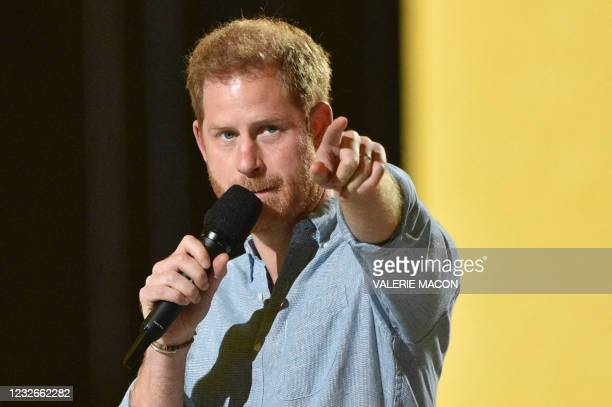 """Co-Chair Britain's Prince Harry, Duke of Sussex, gestures as he speaks onstage during the taping of the """"Vax Live"""" fundraising concert at SoFi..."""
