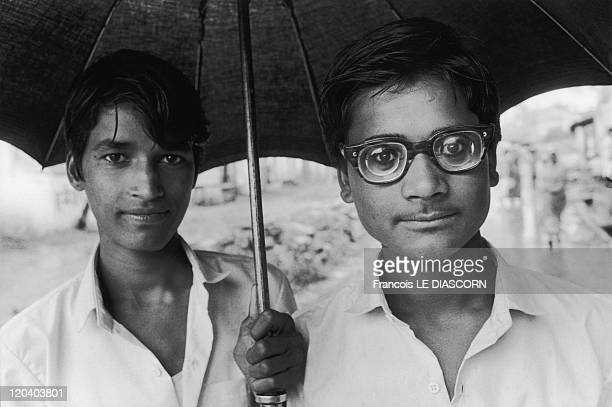 Cochin India Portrait of two friends under the rain one wearing glasses with very thick lenses Kerala