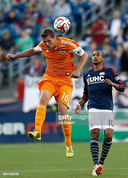 J Cochran of the Houston Dynamos heads the ball by Teal Bunbury of the New England Revolution in the 2nd half at Gillette Stadium on April 12 2014 in...