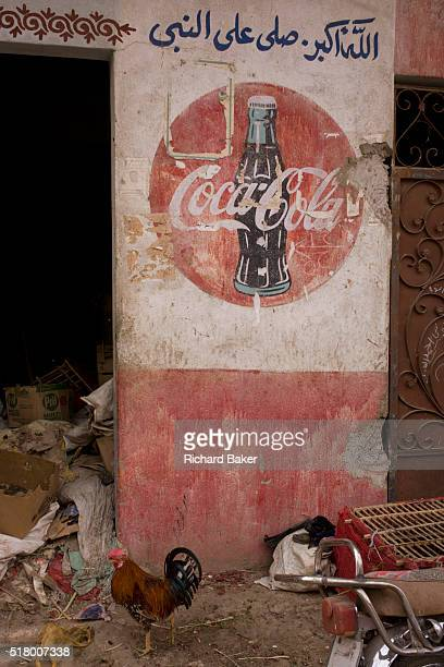 A cock struts under the detail of an old CocaCola mural on a wall at the weekly market at Qurna a village on the West Bank of Luxor Nile Valley Egypt...