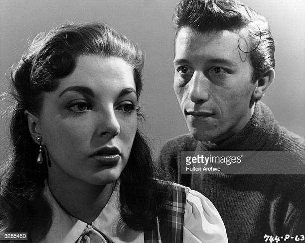 Cockney actor Harry Fowler casts passionate looks at British actress Joan Collins in a scene from the film 'I Believe In You' directed by Basil...