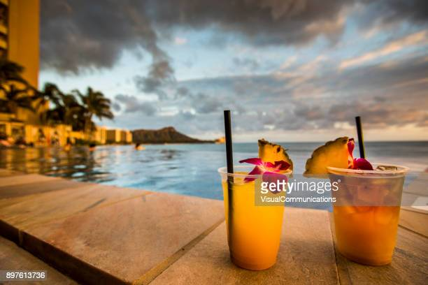 cocktail drinks on beach at sunset. - waikiki stock pictures, royalty-free photos & images
