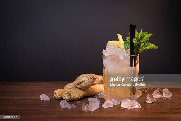 Cocktail Glass And Ginger On Table Against Wall