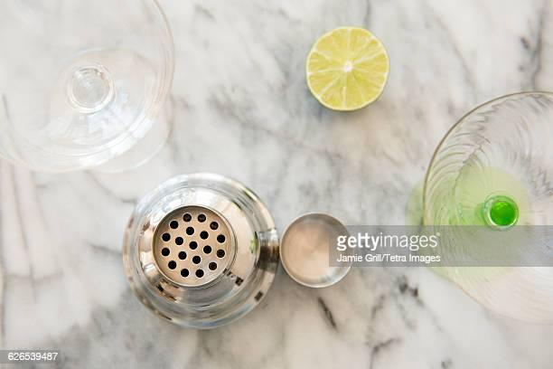 Cocktail in cocktail shaker, martini glasses and halved lime on table