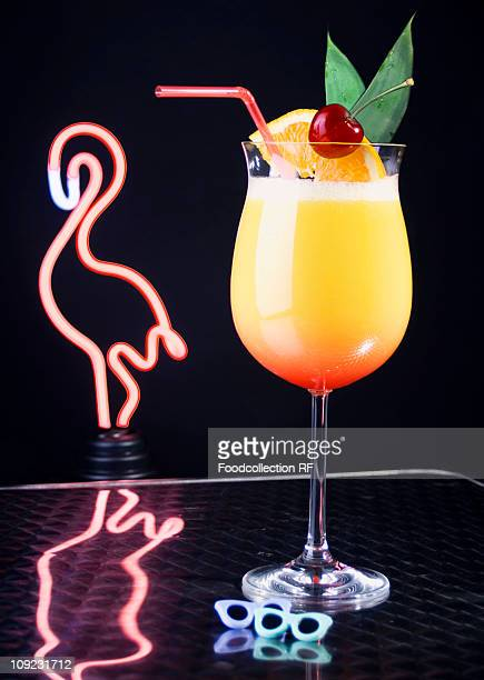 Cocktail in front of neon flamingo light, close-up