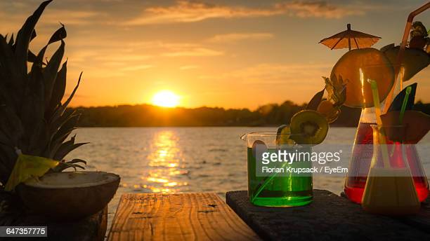 Cocktail In Glasses On Table Against Lake During Sunset