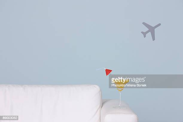 Cocktail on arm of sofa, airplane shape in background