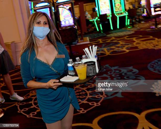 Cocktail server Jem Whalen wears a mask while carrying drinks on the gaming floor at Mandalay Bay Resort and Casino after the Las Vegas Strip...