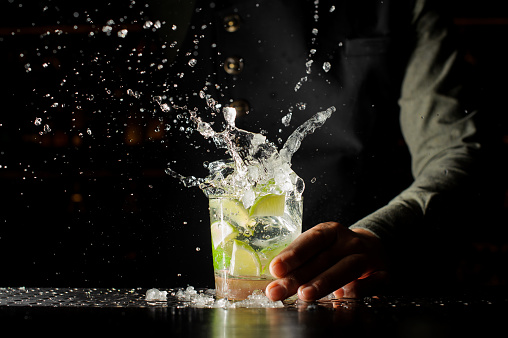 Cocktail splash with ice cubes and lime 938155146