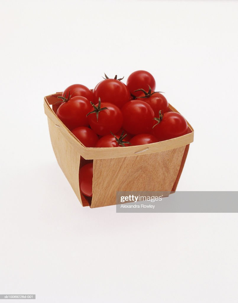 Cocktail tomatoes in basket, studio shot : Stockfoto