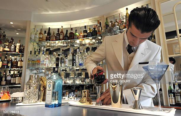 A cocktail waiter makes a drink in the American Bar at the Savoy Hotel in central London England as it reopens following a three year closure for a...