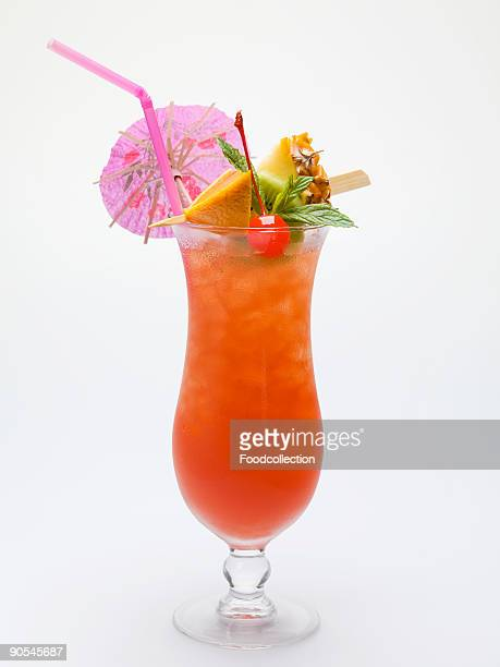 Cocktail with exotic fruit skewer and umbrella, close up