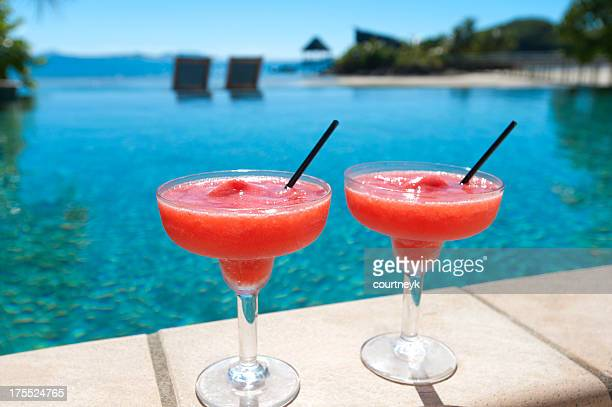2 cocktails beside a resort swimming pool