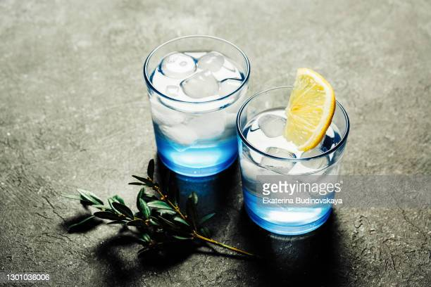 cocktails in blue glasses with ice and lemon - ウォッカ ストックフォトと画像