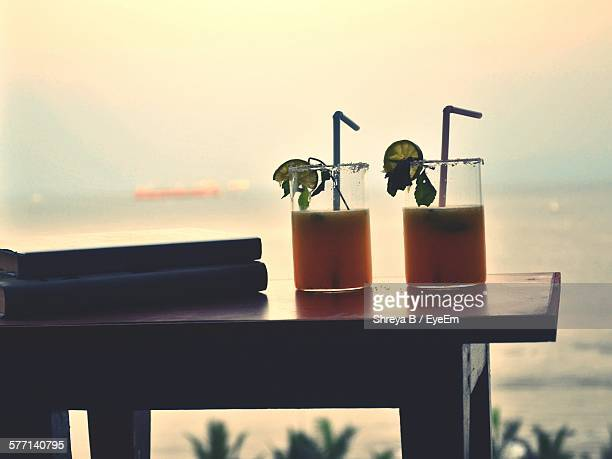Cocktails On Table Against Sea At Sunset