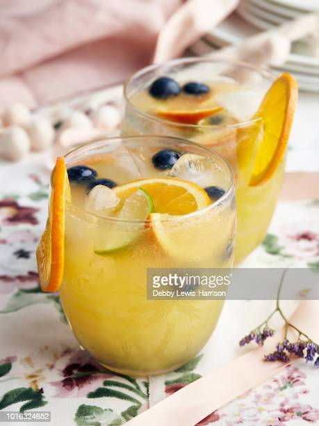 cocktails with orange slices, berries and ice cubes - sangria stock pictures, royalty-free photos & images