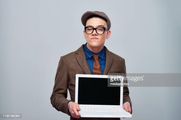 ヴィンテージスーツで生意気なハンサムな男がノートパソコンを保持 - ツイード ストックフォトと画像