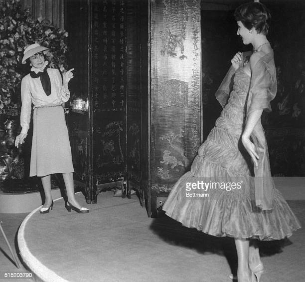 Coco Chanel admires a flounced brown chiffon evening dress from her new collection.