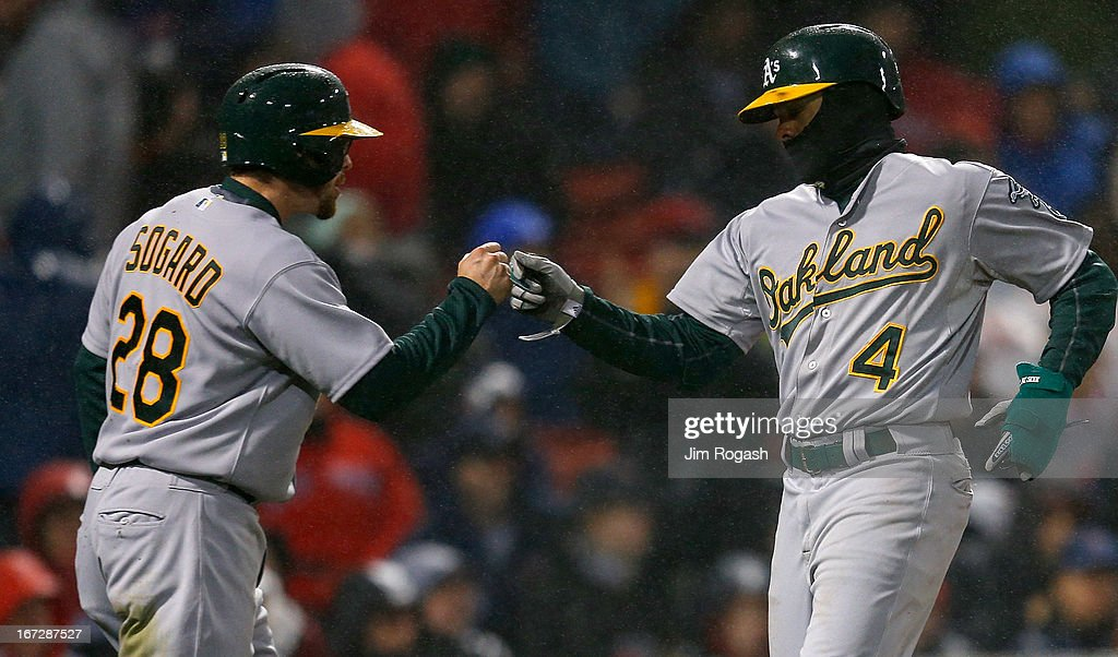 Coco Crisp #4 celebrates scoring a run with Eric Sogard #28 of the Oakland Athletics in the fifth inning against the Boston Red Sox at Fenway Park on April 23, 2013 in Boston, Massachusetts.
