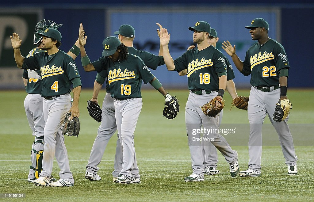 Coco Crisp #4, Jemile Weeks #19, Brandon Hicks #18 and Chris Carter #22 of the Oakland Athletics celebrate the teams win over the Toronto Blue Jays during MLB game action July 24, 2012 at Rogers Centre in Toronto, Ontario, Canada.