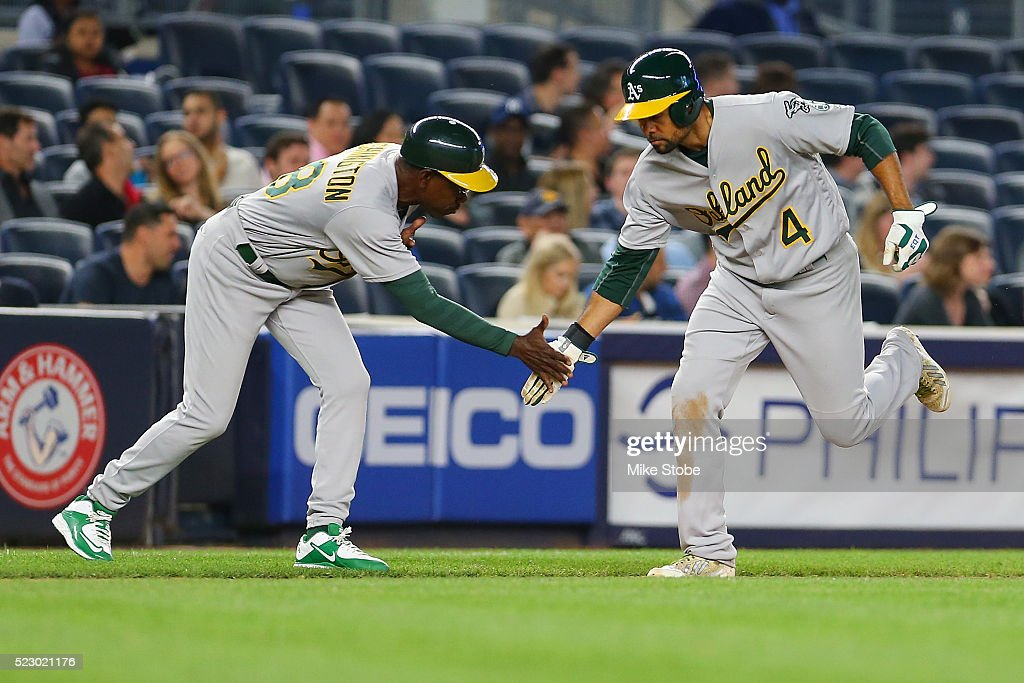 Coco Crisp #4 of the Oakland Athletics celebrates with third base coach Ron Washington #38 after hittinga solo home run in the seventh inning against the New York Yankees at Yankee Stadium on April 21, 2016 in the Bronx borough of New York City.