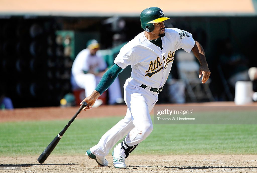 Coco Crisp #4 of the Oakland Athletics hits an RBI single driving in Jemile Weeks #19 against the Texas Rangers in the eighth inning during an MLB baseball game at O.co Coliseum on September 22, 2011 in Oakland, California. The Ahtletics won the game 4-3.