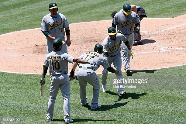 Coco Crisp of the Oakland Athletics is congratulated by his teammates after hitting a grand slam homerun in the fourth inning against the Los Angeles...
