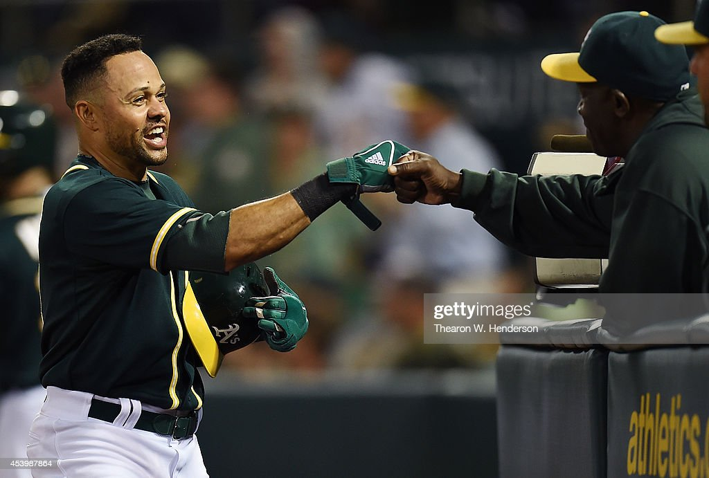 Coco Crisp #4 of the Oakland Athletics is congratulated by hitting coach Chili Davis #30 after he scored on a throwing error by Erick Aybar #2 of the Los Angeles Angels of Anaheim in the bottom of the six inning at O.co Coliseum on August 22, 2014 in Oakland, California.