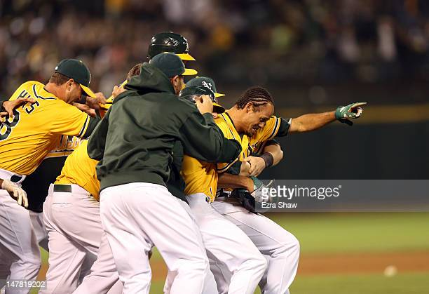 Coco Crisp of the Oakland Athletics is congratulated by teammates after he hit a sacrifice fly that scored Cliff Pennington to beat the Boston Red...