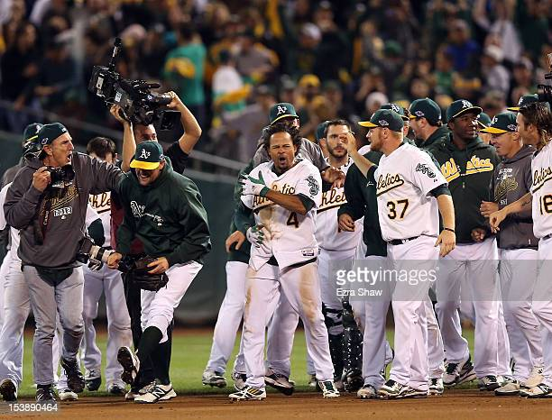 Coco Crisp of the Oakland Athletics is congratulated by teammates after he hit a game-winning single to beat the Detroit Tigers in the ninth inning...