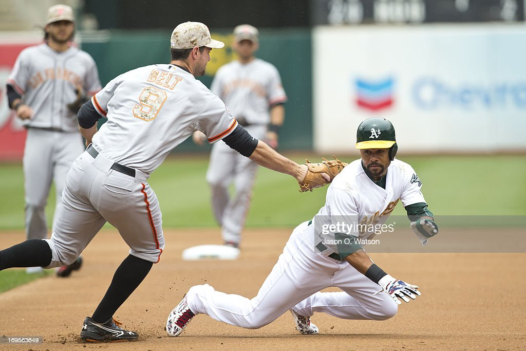 Coco Crisp #4 of the Oakland Athletics is tagged out by Brandon Belt #9 of the San Francisco Giants on a pickoff play during the first inning of the interleague game at O.co Coliseum on May 27, 2013 in Oakland, California.
