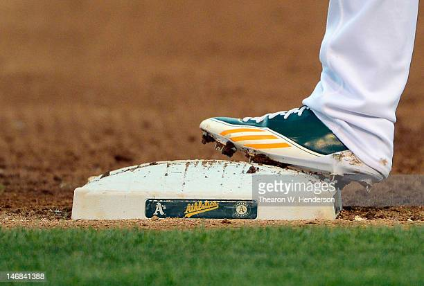 Coco Crisp of the Oakland Athletics makes wearing adidas cleats stands on first base against the Los Angeles Dodgers at Oco Coliseum on June 19 2012...