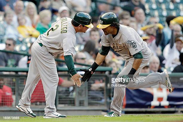 Coco Crisp of the Oakland Athletics receives congratulations from third base coach Mike Gallego after hitting a home run in the fourth inning against...