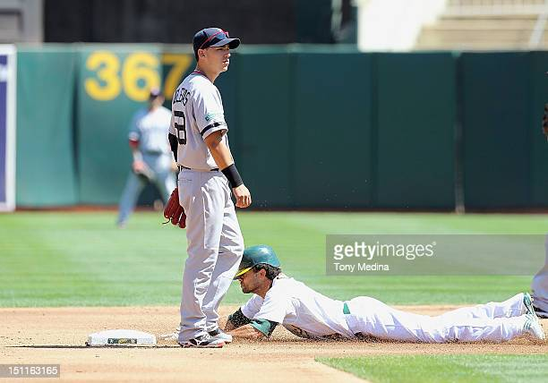 Coco Crisp of the Oakland Athletics safely steals second base as Jose Iglesias of the Boston Red Sox looks to the catcher for the throw during a game...