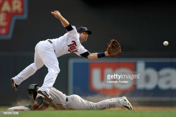 Coco Crisp of the Oakland Athletics steals second base as Brian Dozier of the Minnesota Twins fields the ball during the fifth inning of the game on...