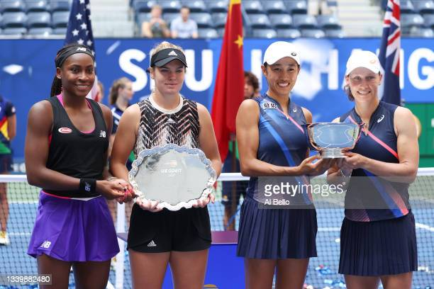 Coco Gauff of the United States and Catherine McNally of the United States smile with the runner-up trophy alongside Shuai Zhang of China and...