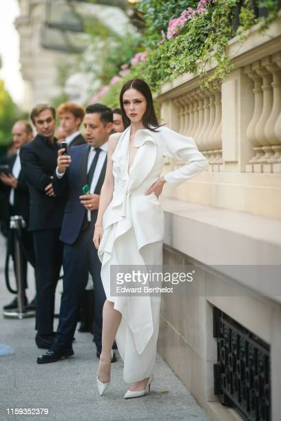 Coco Rocha wears a one-sleeve white long dress with flounces, white pointy heeled pumps, outside AMFAR dinner, during Paris Fashion Week - Haute...