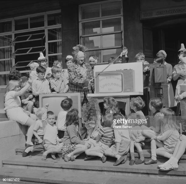 Coco the Clown, aka Nicolai Poliakoff cuts a cake in the shape of a television set at Great Ormond Street Hospital in London, to mark the...