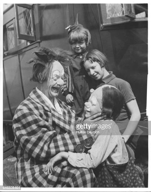 Coco the Clown the Bertram Mills Circus' worldfamous entertainer paints the face of his son Michael watched by two of his daughters Alexandra and...