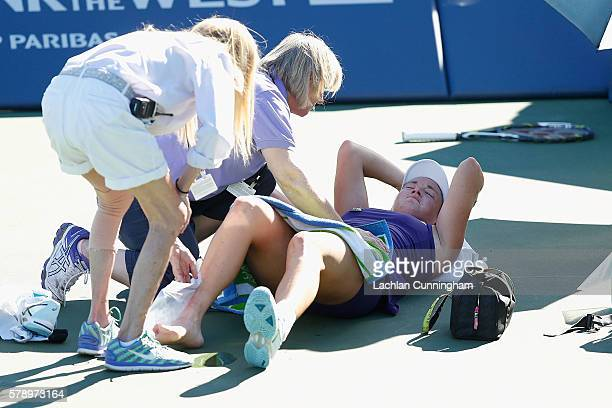 CoCo Vandeweghe of the United States is assisted by trainers after injuring her ankle in her match against Alison Riske of the United States during...