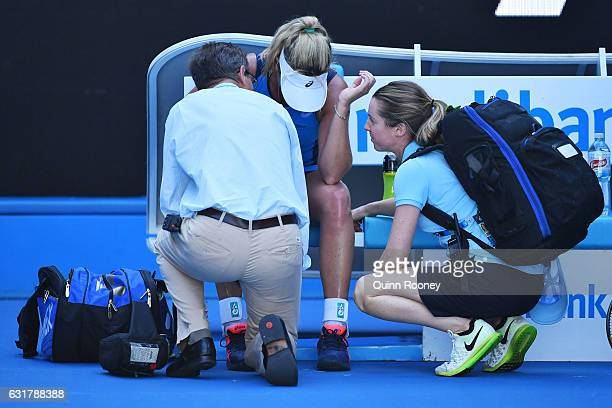 Coco Vandeweghe of the United States is attended to by medical staff after winning her first round match against Roberta Vinci of Italy on day one of...