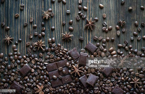Cocoa beans and chocolate bars on wooden table