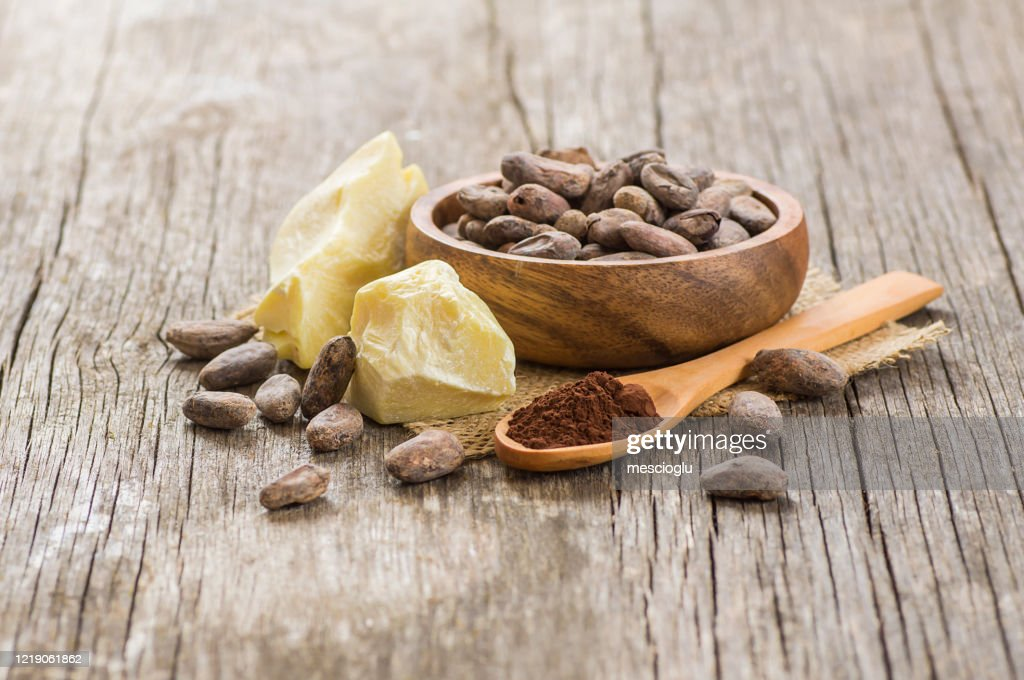 Cocoa butter or Cocoa bean solid oil with cacao powder in spoon and raw cocoa beans in wooden bowl on rustic backdrop, healthy natural oil : Stock Photo
