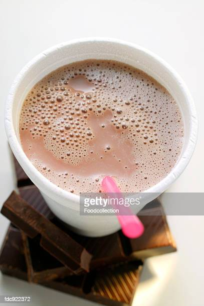Cocoa in paper cup with straw on pieces of chocolate