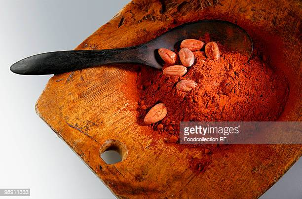 Cocoa powder and cocoa beans on wooden board with spoon.