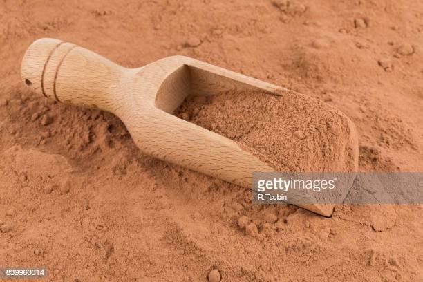 cocoa powder in wooden scoop