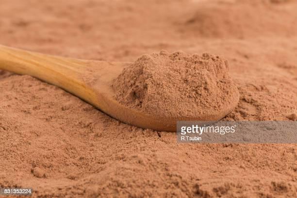 cocoa powder in wooden spoon