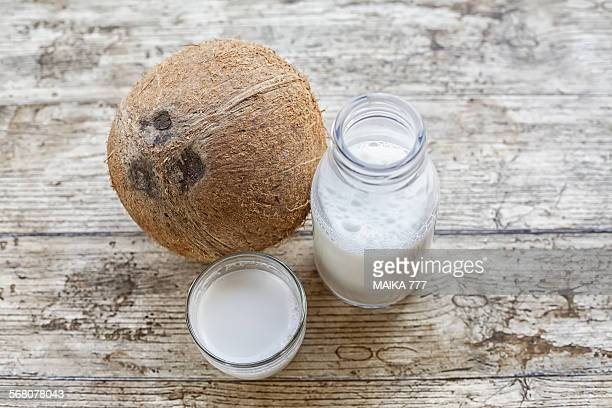 Coconut fruit and coconut milk on wooden surface